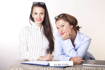 Portrait of a two young beautiful female receptionists with a sign. Stock Photo - 16238402