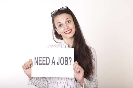 Portrait of a young beautiful woman holding a sign need a job. Stock Photo