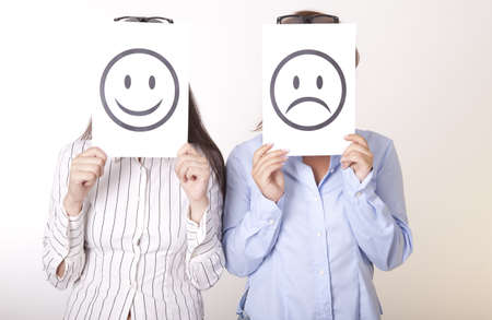 Portrait of a two young women holding smiley and sad smiley face. photo
