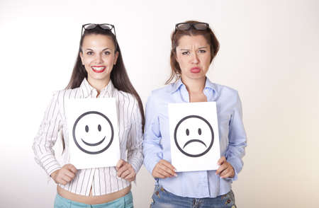 Portrait of a two young beautiful women holding smiley and sad smiley face. Stock Photo