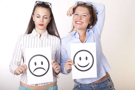 Portrait of a two young beautiful women holding smiley and sad smiley face. photo