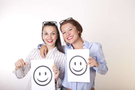 Portrait of a two young beautiful women holding smiley faces. photo