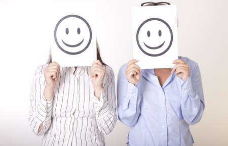 Portrait of a two young beautiful women holding smiley faces.