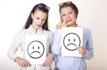 Portrait of a two young beautiful women holding sad smiley faces.