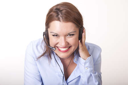 Portrait of a young beautiful secretary with headphones smiling.