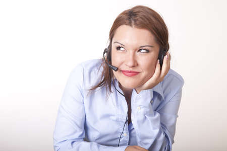 Portrait of a young beautiful secretary with headphones thinking. Stock Photo