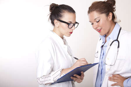 Portrait of a two young beautiful female doctors working. photo