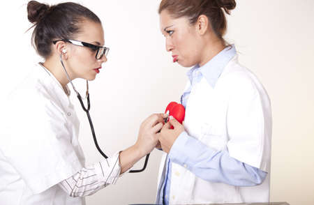Portrait of a two young beautiful female doctors checking a red heart.