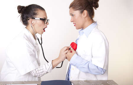 Portrait of a two young beautiful female doctors checking a red heart. photo