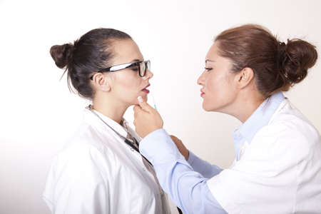 Portrait of a two young beautiful female doctors holding syringe. Stock Photo