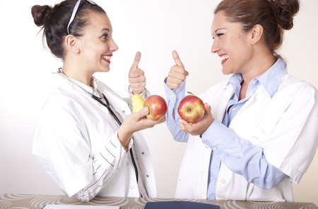 Portrait of a two young beautiful female doctors with apple showing thumb up.