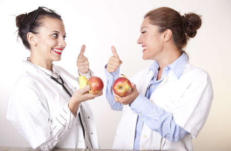 Portrait of a two young beautiful female doctors holding apples showing thumb up.