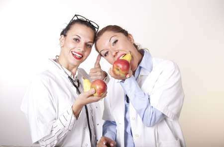 Portrait of a two young beautiful female doctors holding fruits.