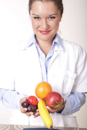 Portrait of a young beautiful female doctor holding fruits and smiling. photo