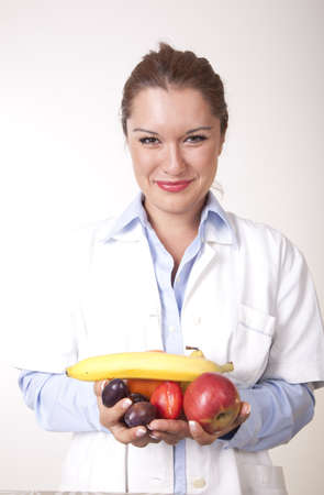 Portrait of a young beautiful female doctor holding fruits and smiling.