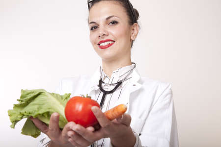 Portrait of a young beautiful female doctor holding fresh vegetables.
