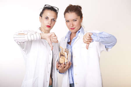 Portrait of a two young beautiful female doctors holding cookies.
