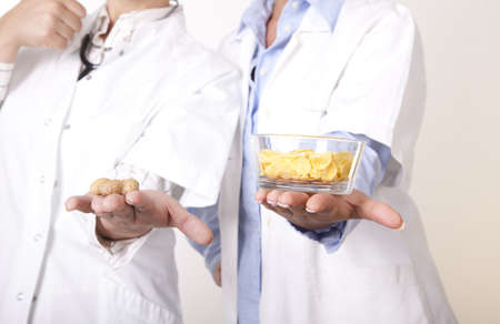 Portrait of a two young beautiful female doctors holding peanuts and cornflakes.