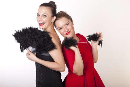 Portrait of a two beautiful women in fancy dresses holding handcuffs.