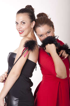Portrait of a two beautiful women in fancy dresses holding handcuffs. Stock Photo - 16238276