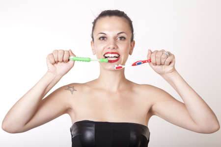 Portrait of a young beautiful woman cleaning her teeth with toothbrushes  photo