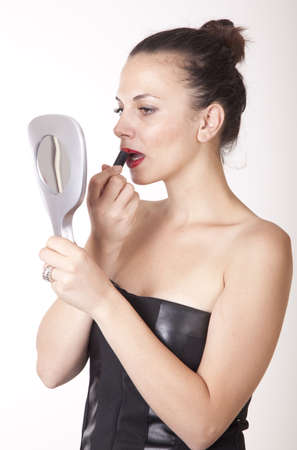 Portrait of a young beautiful woman putting on red lipstick  photo