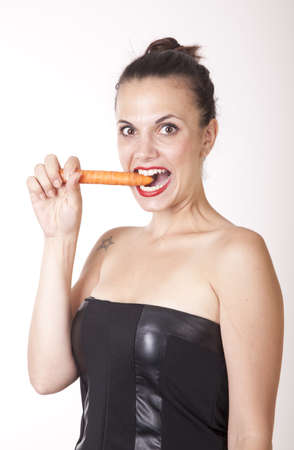 Portrait of a young beautiful woman eating carrot  photo