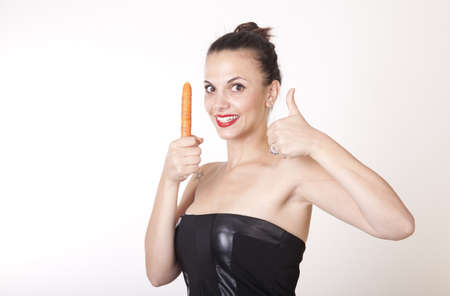 Portrait of a young beautiful woman holding a carrot  photo