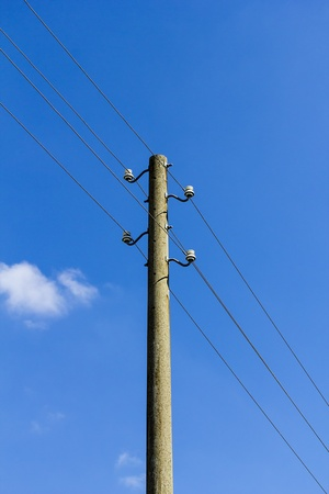 old concrete power-line isolated on blue sky. photo