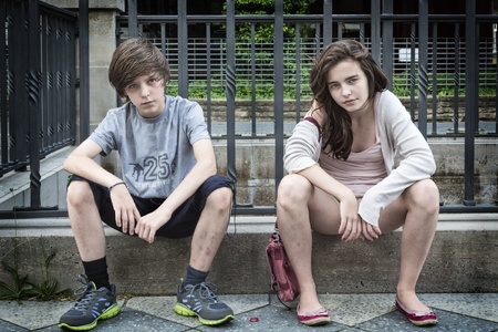 two dirty urban teens sitting on a wall. photo