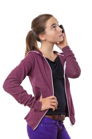 teenage girl speaking on mobile phone, looking into the sky, isolated on white. photo