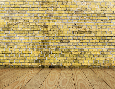 indoor background with yellow brick wall and wooden plank floor. photo
