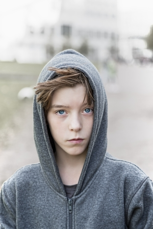 portrait of a teenage boy with grey hoodie sweatshirts. photo