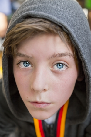 portrait of a teenage boy with grey hoodie sweatshirts, after sports with red face. photo