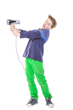 casual teenage boy is fighting with a hair dryer, isolated on white. photo