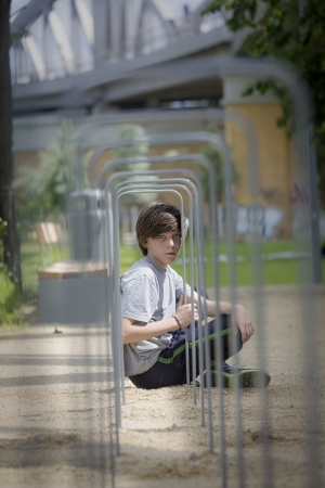 portrait of a teenager boy sitting behind a metal frame. photo