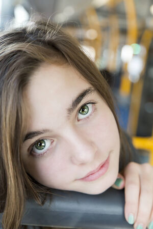 portrait of a beautiful teenager girl, sitting in a bus. photo