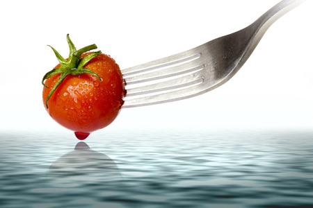 �spiked: tomate cherry pinchos por un tenedor, con reflejo en el oc�ano, aislado en blanco. Foto de archivo