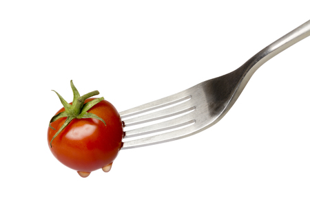 spiked: cherry tomato spiked by a fork , isolated on white. Stock Photo