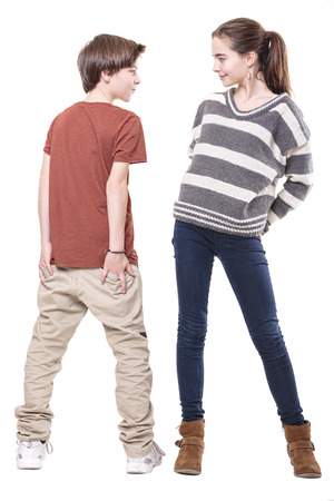 two teenager, male and female smiling at each other, isolated on white. Standard-Bild