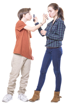 mutually: two teenager mutually kissing their mobile phones, isolated on white. Stock Photo