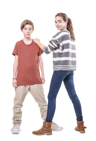 mutually: teenager siblings girl holding the shoulder of here brother, isolated on white.