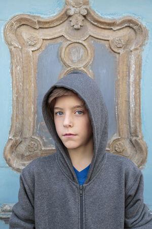 hoody: Портрет мужчины подросток с серым капюшоном в передней части декоративной двери.