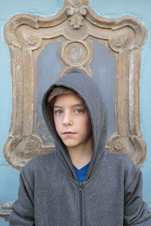 portrait of a male teenager with gray hoody in front of a ornamental door. photo