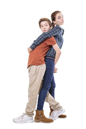 mutually: teenager siblings hugging back on back, isolated on white.
