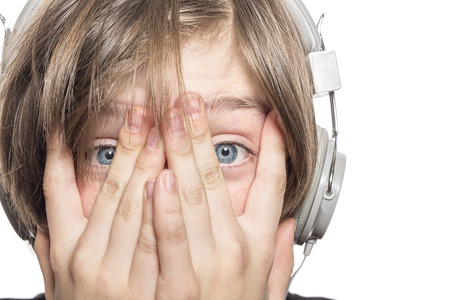 desperate male teenager with headphones covering his face with hands, isolated on white photo