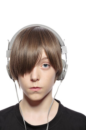 teenager boy with hair over one eye and headphones, isolated on white. photo