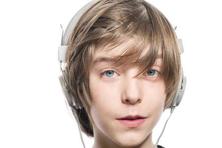 eager: smiling cute teenager boy with headphones, isolated on white.