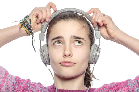 beautiful teenager girl fumble on her headphones, isolated on white. photo