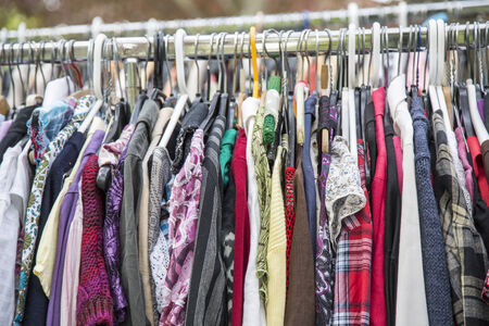 garage sale: clothes on a rack in a flea market .